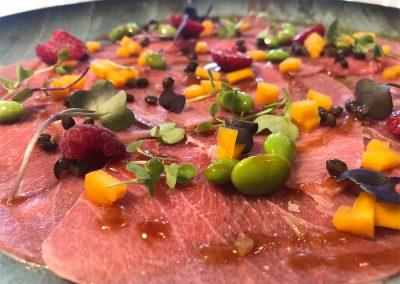 Carpaccio de ventresca de atún, reducción de soja y naranja y crudites de temporada